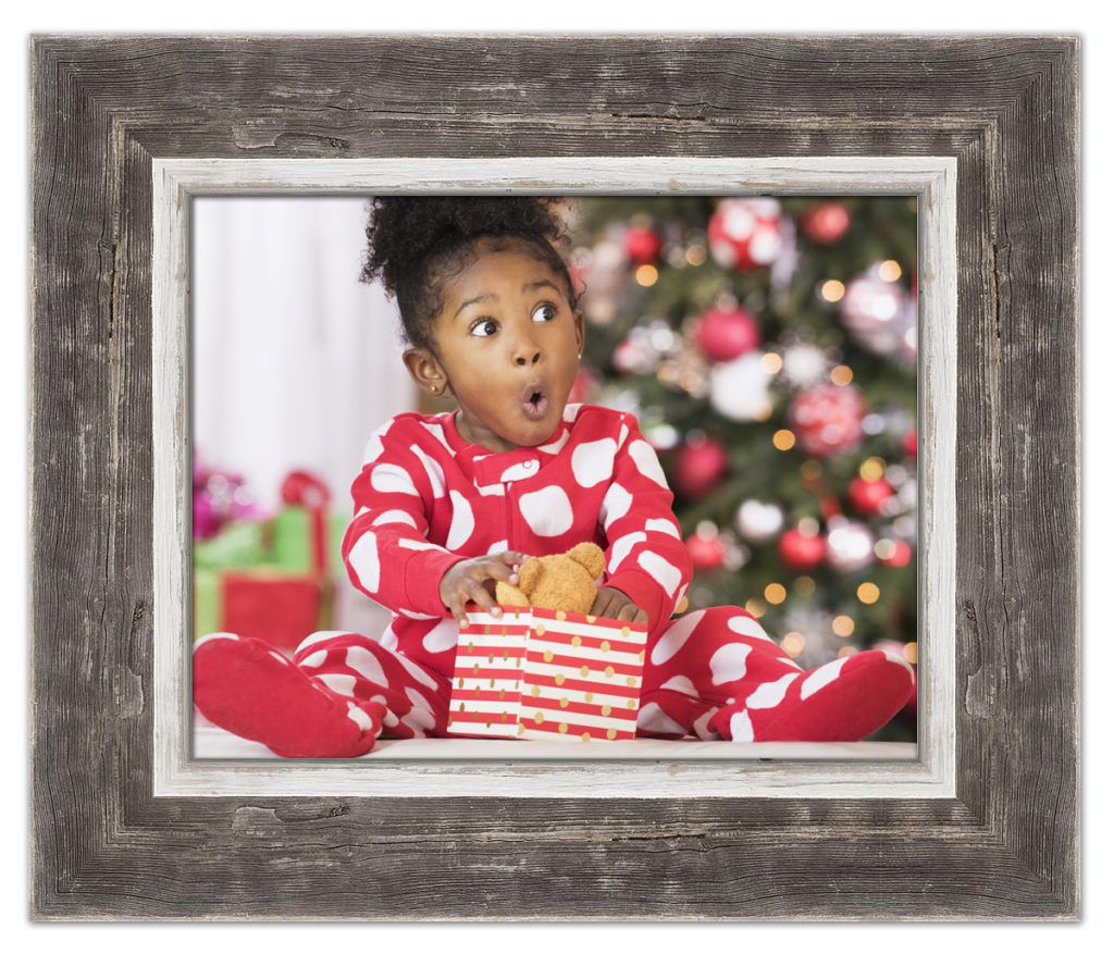 little girl opening present in barnwood frame